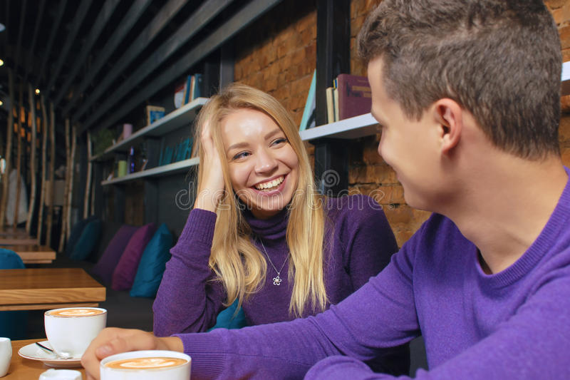 Loving young couple sitting in the cafeteria. Talking and smiling. Drink hot coffee stock image