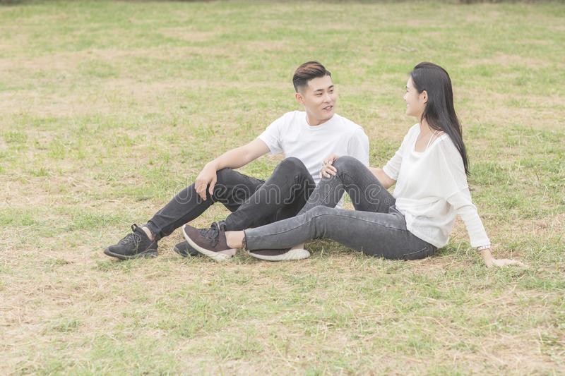 Loving young couple sitting down on grass stock images