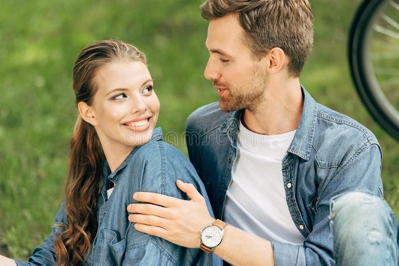 loving young couple sitting on grass stock photography