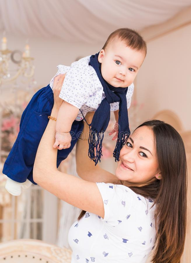 Loving young mother holding her son indoors royalty free stock photos