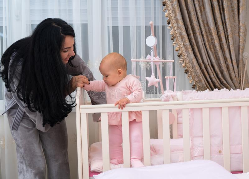 Loving young mother teaching her baby to stand. royalty free stock photo