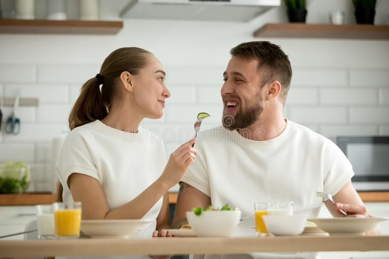 Loving young wife feeding bearded husband during breakfast at ho stock images