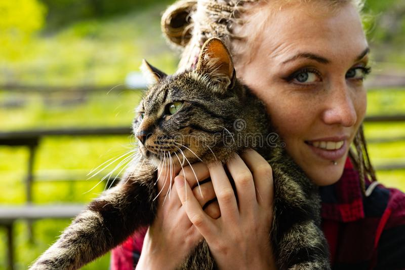 Loving young woman cuddling her cat to her cheek. With a happy smile outdoors in a summer garden in a close up cropped portrait royalty free stock photo