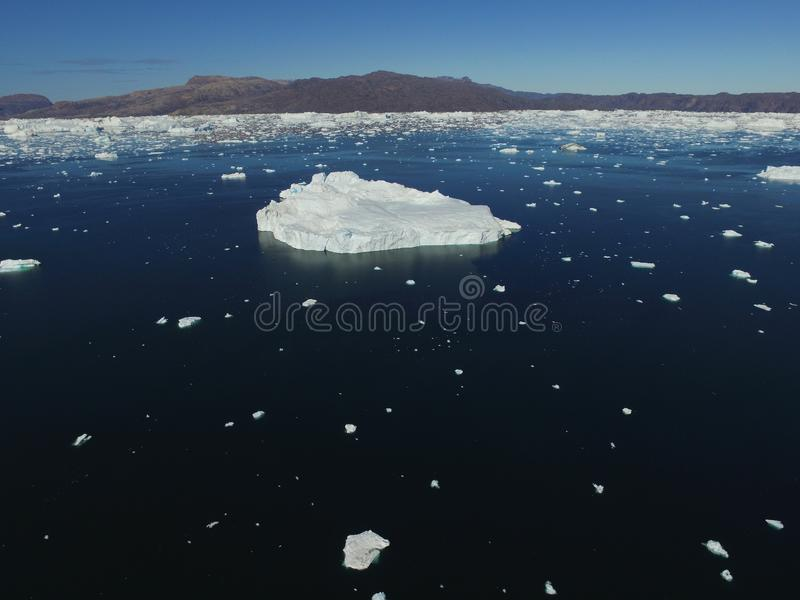 Low altitude oblique drone aerial image of a large iceberg surrounded by many smaller icebergs near Upernavik, Greenland royalty free stock photography