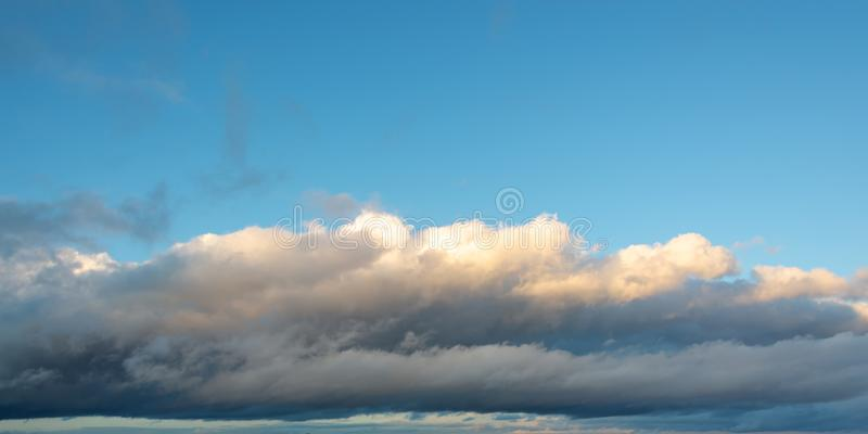 Low altitude stratocumulus cloud under blue sky, panoramic nature background. Low altitude stratocumulus cloud under a blue sky, panoramic nature background stock image