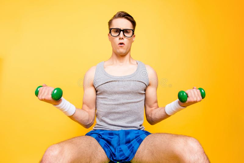 Low angel view portrait of strong youth man raises green dumbbel stock image