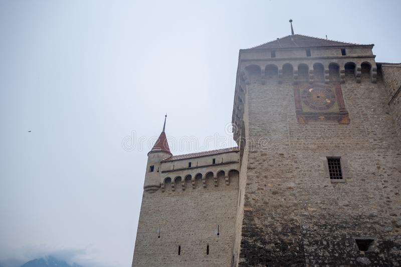 Low angle of beautiful clock tower in chateau de chillon, castle in Montreux Switzerland, on cloudy sky background. With copy space stock photo