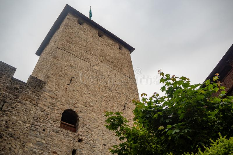Low angle of beautiful tower with top of lush tree in chateau de chillon, castle in Montreux Switzerland, on cloudy sky background. With copy space royalty free stock photos