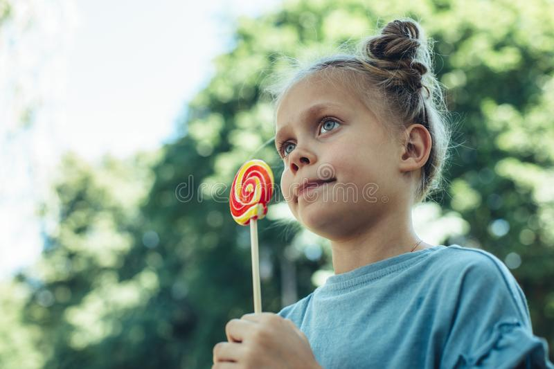 Happy kid holding candy in park stock photos