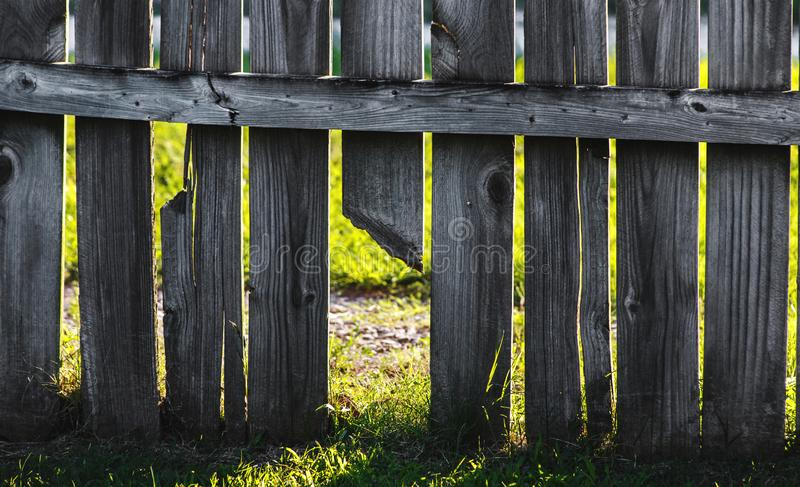 Sunlight Breaking and Entering. Low angle closeup shot of a section of wooden fence where a broken board at the bottom is allowing sunlight to stream in onto the royalty free stock image