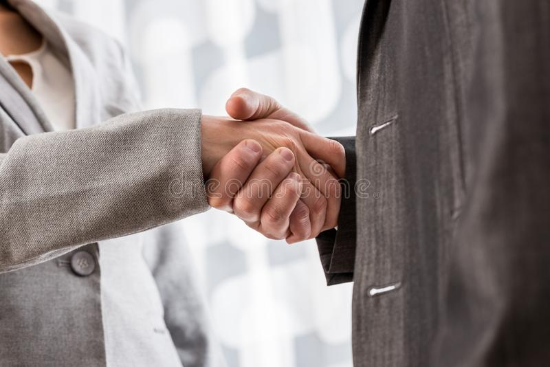 Low angle closeup view of a business handshake. Low angle closeup view of male and female business partners shaking hands royalty free stock photos