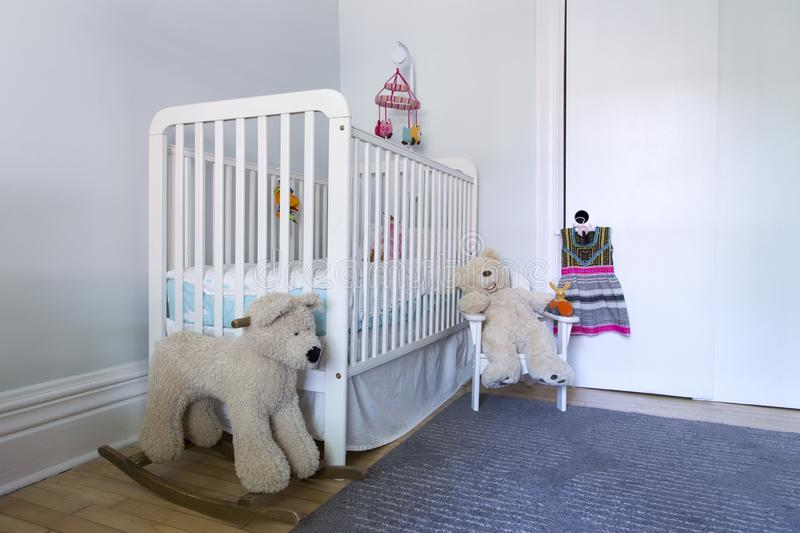 Low angle corner view of pretty pale baby room with stuffed teddy bear toys royalty free stock photo