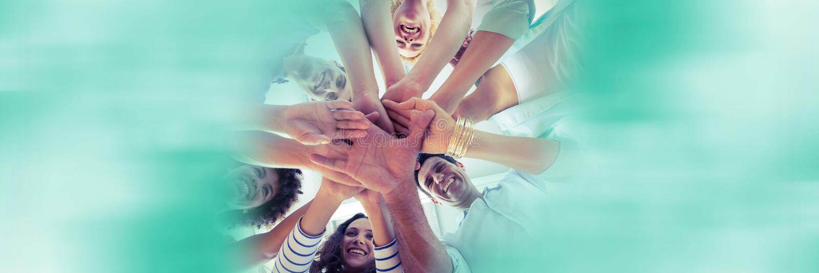Low angle of creative team and putting hands together and blurry teal framing royalty free stock image