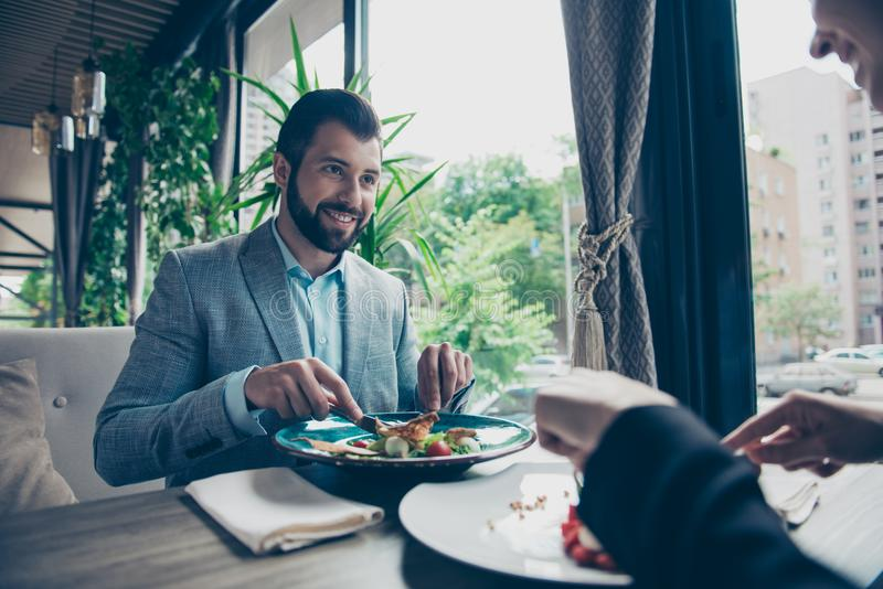Low angle cropped photo of a brunet guy stting in a fancy restaurant`s terrace with view, in a formalwear and smiling, looking. At his lady, having salad royalty free stock photography