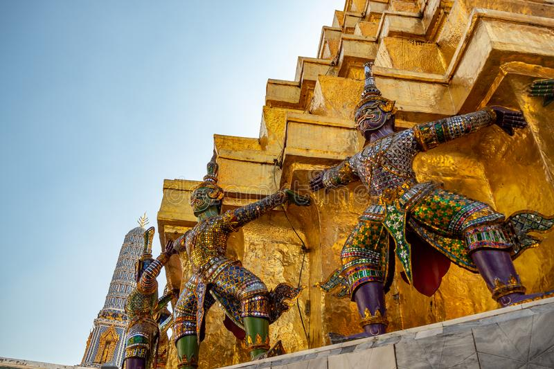Low angle of giant statues on the base of golden pagoda in royal temple in grand palace with clear blue sky background stock photo