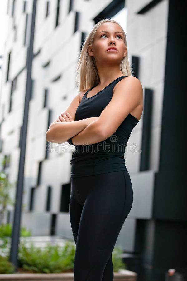 Fit Woman with Arms Crossed Standing Against Futuristic Modern Building In City royalty free stock images
