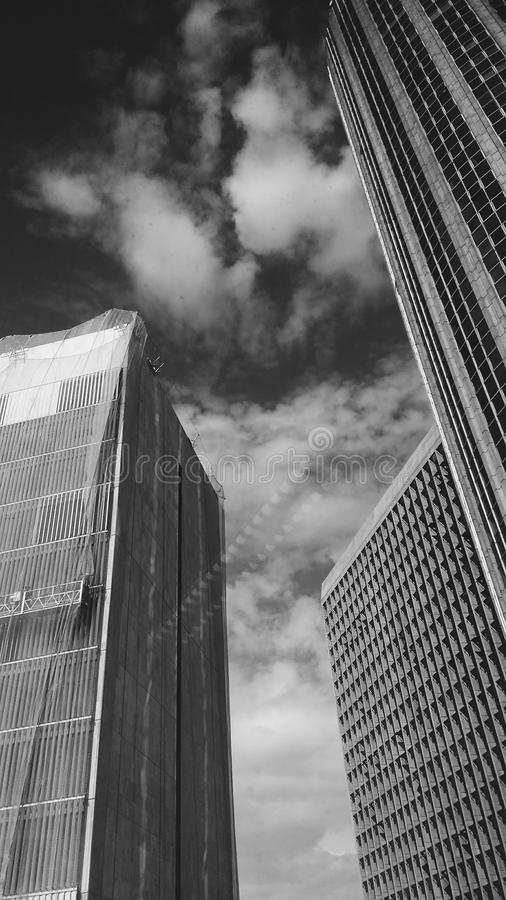 Low Angle Grayscale Photography of Buildings and Clouds stock images