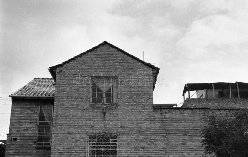 Low angle grey scale shot of an old brick building under the cloudy sky. A low angle grey scale shot of an old brick building under the cloudy sky stock photos