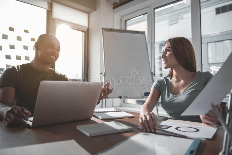 Glad man and woman discussing project in conjunction royalty free stock photo