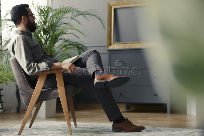 Low angle of hipster sitting on wooden armchair in grey vintage royalty free stock photography