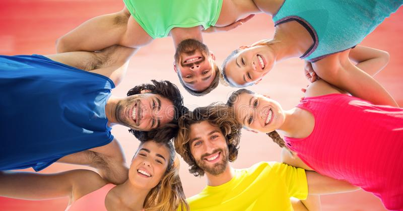 Low angle of millennials in circle against blurry red background. Digital composite of Low angle of millennials in circle against blurry red background stock photo