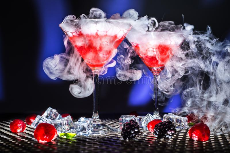 Low angle modern view dessert show or glass of red cocktail and smoke or dry ice steam, ice cubes blackberrys raspberries mint on royalty free stock images