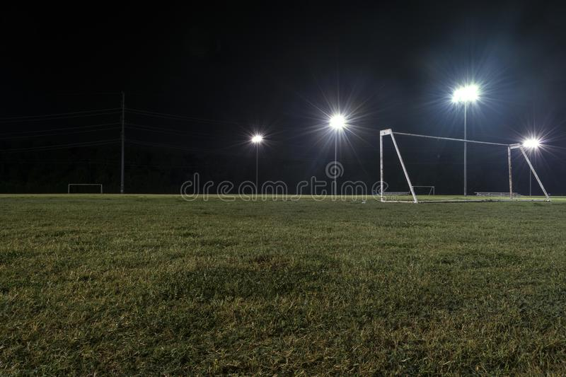 Low angle night photo of goal on empty soccer field stock images