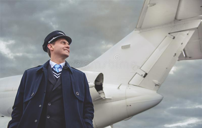 Cheerful aviator situating near aircraft stock images