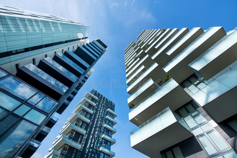 Low angle perspective of modern Milan skyscrapers. Low angle converging perspective of modern Milan skyscrapers with large balconies against a clear sunny blue royalty free stock photos