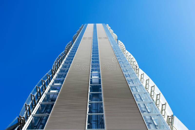 Low angle perspective of a modern skyscraper. With external decorative cladding on the side walls against a clear sunny blue sky royalty free stock images