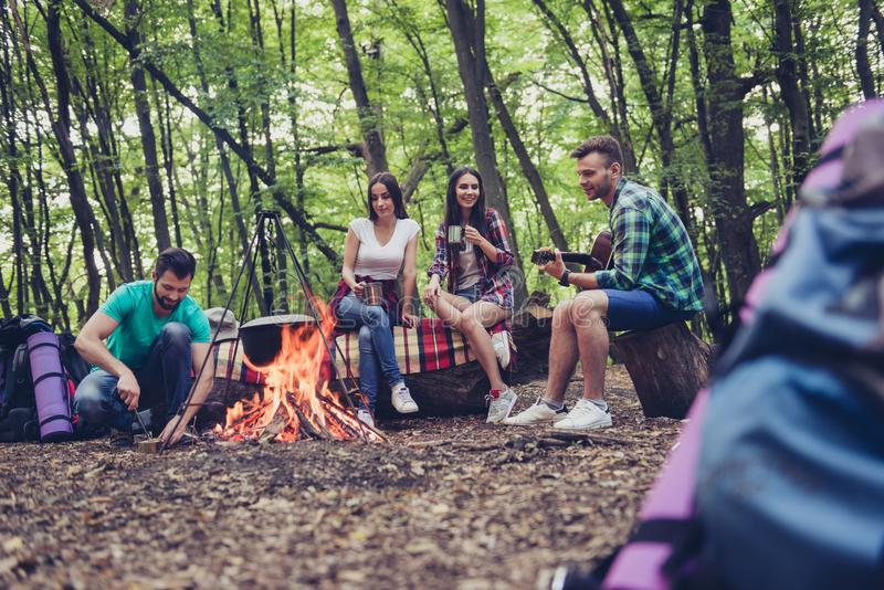 Low angle photo of fire place, four serene tourists are sitting. Around, girls drink tea, guys play guitar and open the canned goods, nice wood view royalty free stock photography