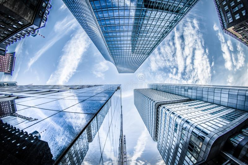 Low-angle Photo of Four High-rise Curtain Wall Buildings Under White Clouds and Blue Sky royalty free stock photos