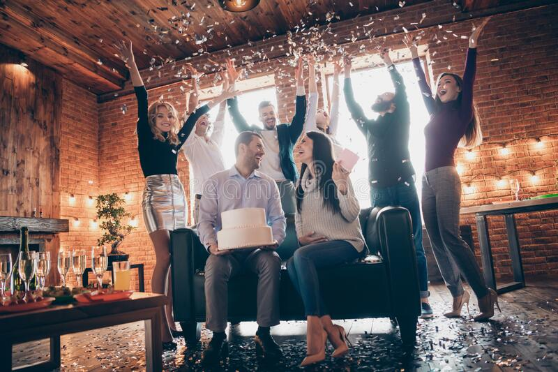 Low angle photo of group amazing eight friends throwing confetti meeting surprise baby party future parents sit sofa stock images