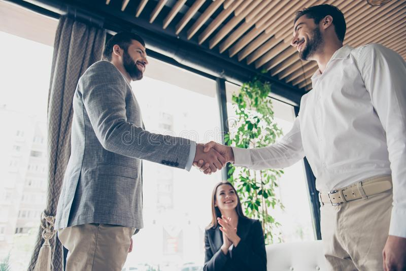 Low angle photo of three business partners in formal outfits mad. E a deal about their business. Men are shaking hands to complete the deal, lady is happy royalty free stock photography
