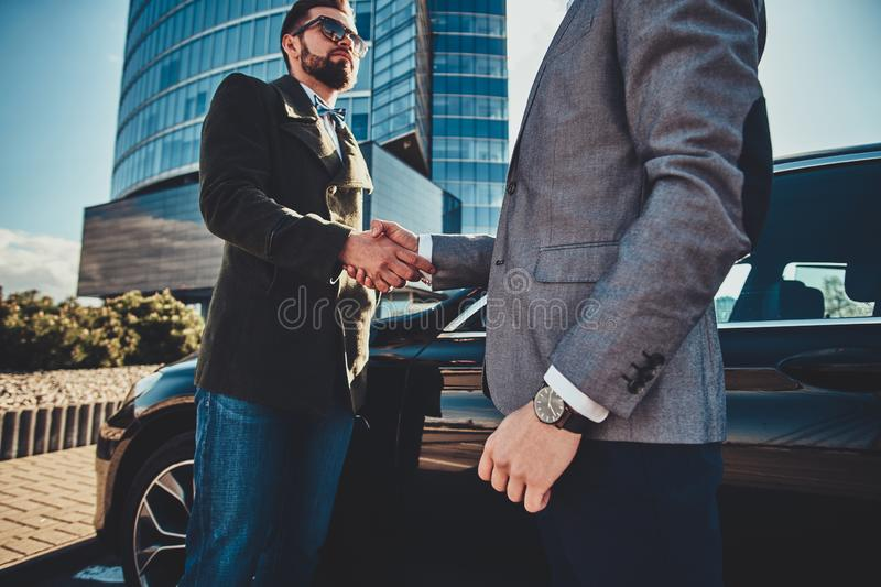 Low angle photo of two smart elegant men, which have a deal about car stock images