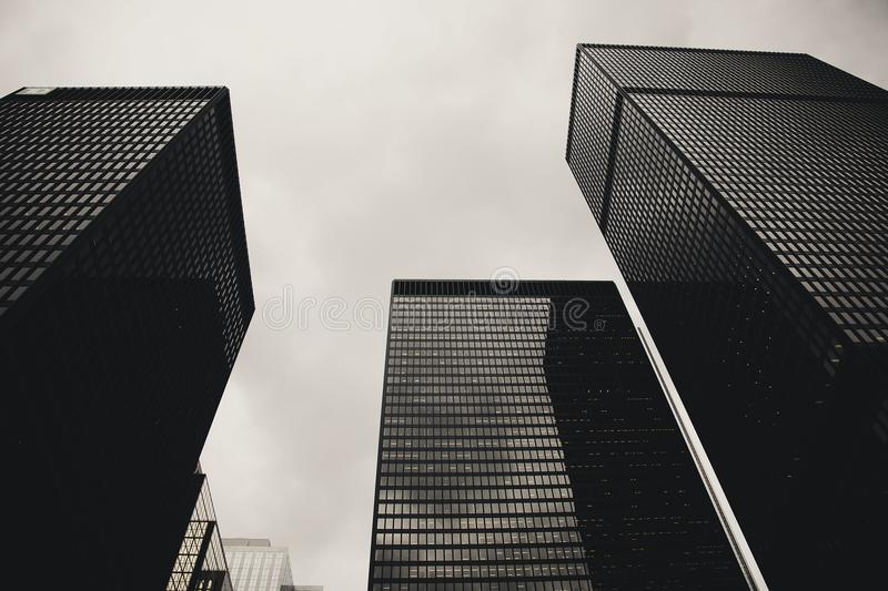 Low Angle Photography of Black High Rise Building Under Nimbus Clouds Background royalty free stock images