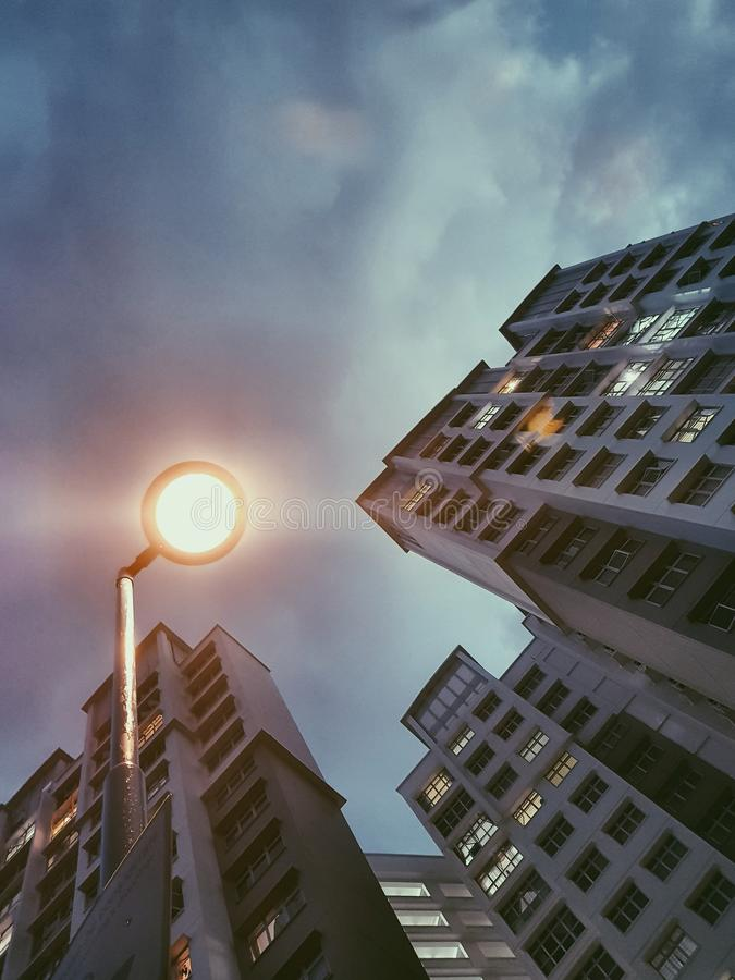 Low Angle Photography of Lamp Post Beside Building Under Cloudy Sky royalty free stock image