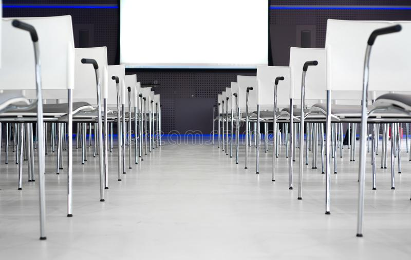 Low Angle Photography of Pile of Stainless Steel Chairs With Hanging Projector Canvas stock images