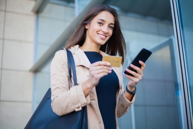 Low Angle Of Pleased Girl Standing at the Airport Hall. He is Using Gold Credit card and Cellphone For Paying stock image