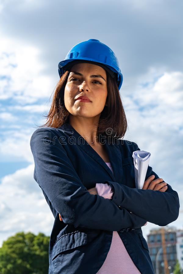 Charming and successful woman architect posing with folded arms. Low-angle shot. Low angle portrait of a beautiful and successful lady architect wearing a blue royalty free stock photo