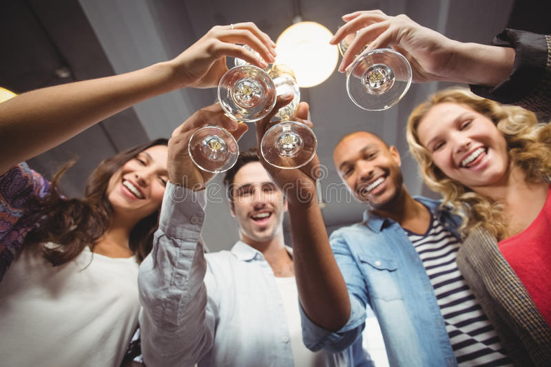 Low angle portrait of cheerful colleagues toasting in office stock photo