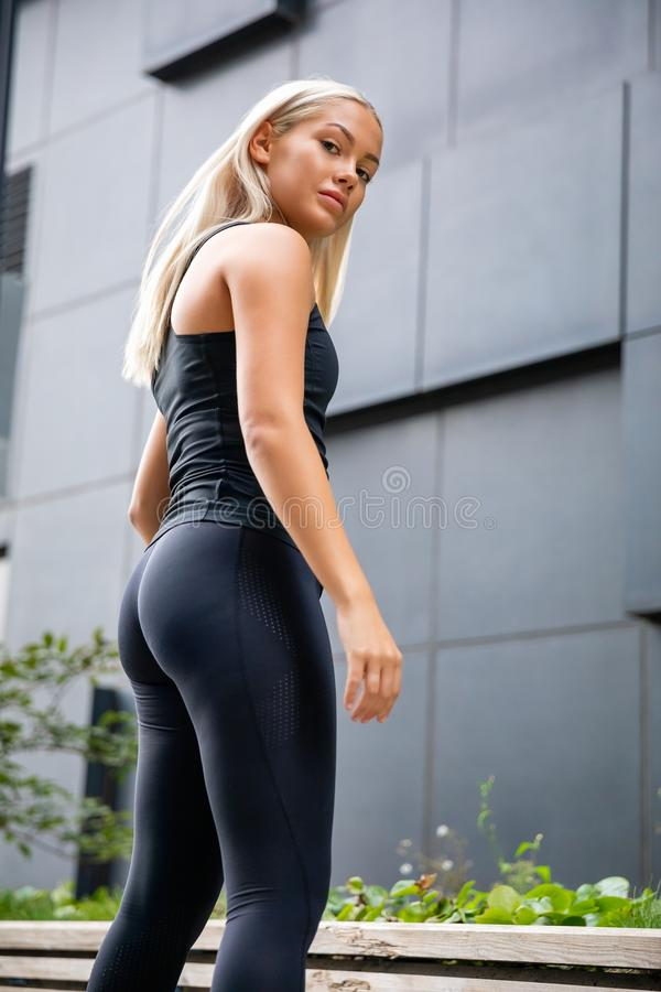 Confident and determined Female Athlete Standing Against Building stock image