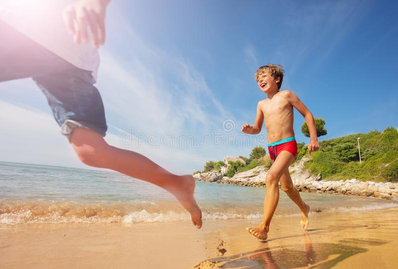 Happy boy playing beach games with friends stock photos