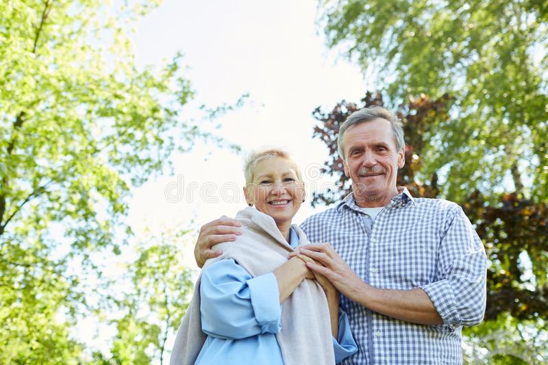 Smiling Senior Couple Walking in Park stock images