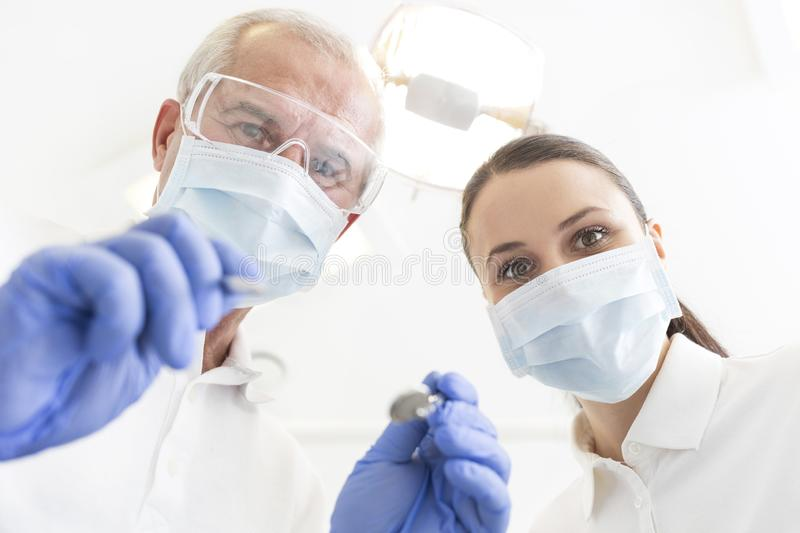 Low angle portrait of male and female dentists wearing masks at dental clinic royalty free stock photos