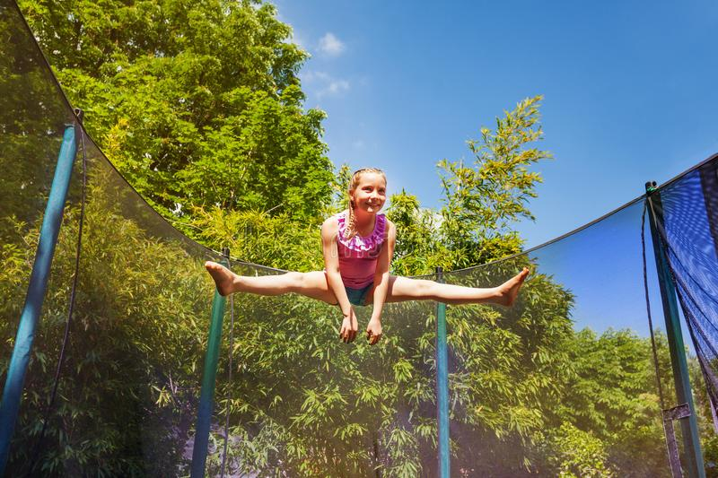 Happy girl performing split jump on the trampoline royalty free stock photo