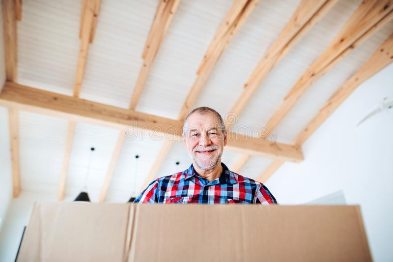 A low-angle portrait of senior man furnishing new house, a new home concept. stock photo