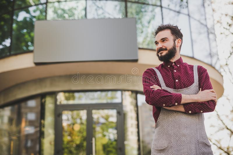 Confident waiter standing outside cafe. Low angle of positive bearded man in apron smiling and looking away while standing with crossed arms outside modern royalty free stock image