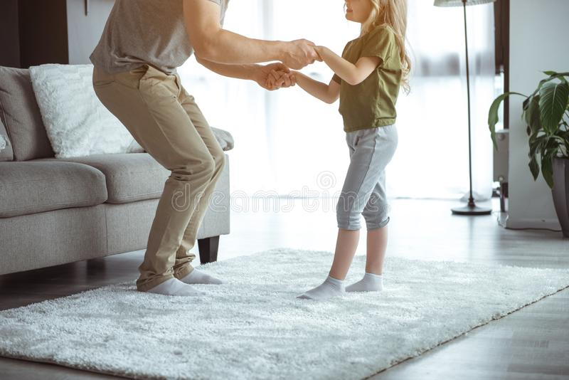 Joyful father dancing with his small daughter on rug stock photos