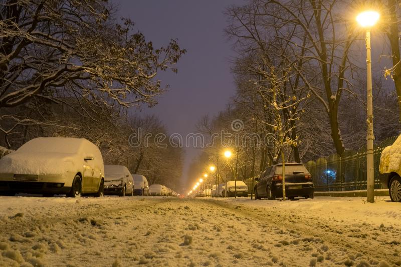 Low angle of rows of parked cars at night, covered with snow, on a narrow street, after a heavy snowfall in Winter time royalty free stock images